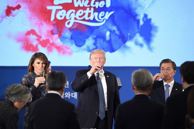 "US President Donald Trump (C), South Korea's President Moon Jae-In (R) and US First Lady Melania Trump (L) take a drink during a state dinner at the presidential Blue House in Seoul on November 7, 2017. North Korea poses a worldwide threat that requires worldwide action, President Donald Trump said in Seoul on November 7, but insisted ""we are making a lot of progress"" in reining in the rogue state. / AFP PHOTO / Jim WATSON (Photo credit should read JIM WATSON/AFP/Getty Images)"