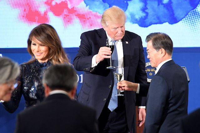 """US President Donald Trump (C) toasts South Korea's President Moon Jae-In (R) near US First Lady Melania Trump during a state dinner at the presidential Blue House in Seoul on November 7, 2017. North Korea poses a worldwide threat that requires worldwide action, President Donald Trump said in Seoul on November 7, but insisted """"we are making a lot of progress"""" in reining in the rogue state. / AFP PHOTO / Jim WATSON (Photo credit should read JIM WATSON/AFP/Getty Images)"""