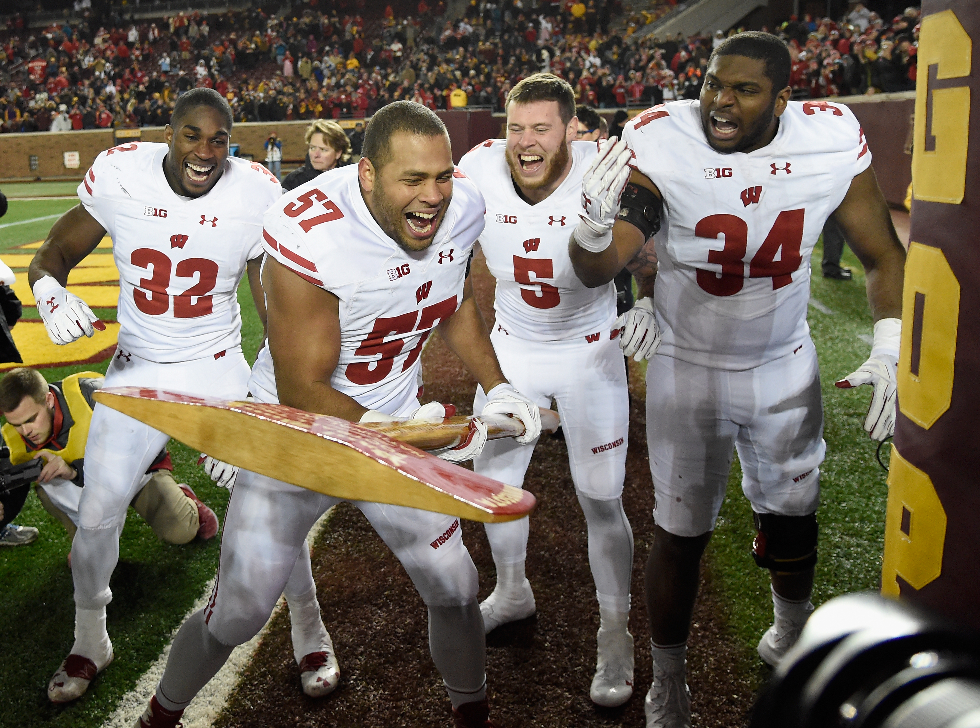 MINNEAPOLIS, MN - NOVEMBER 25: Leon Jacobs #32, Garret Dooley #5, Chikwe Obasih #34 of the Wisconsin Badgers cheer on teammate Alec James #57 as he pretends to chop down the goal post with Paul Bunyan's Axe after defeating the Minnesota Golden Gophers in the game on November 25, 2017 at TCF Bank Stadium in Minneapolis, Minnesota. The Badgers defeated the Golden Gophers 31-0. (Photo by Hannah Foslien/Getty Images)