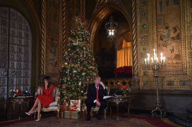 """US President Donald J. Trump and the First Lady Melania Trump participate in NORAD Santa Tracker phone calls at the Mar-a-Lago resort in Palm Beach, Florida on December 24, 2017. """"NORAD Tracks Santa"""" is an annual Christmas-themed entertainment program, which has existed since 1955, produced under the auspices of the North American Aerospace Defense Command. / AFP PHOTO / Nicholas Kamm (Photo credit should read NICHOLAS KAMM/AFP/Getty Images)"""