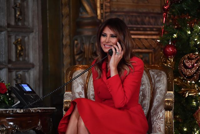 """First Lady Melania Trump participates in NORAD Santa Tracker phone calls at the Mar-a-Lago resort in Palm Beach, Florida on December 24, 2017. """"NORAD Tracks Santa"""" is an annual Christmas-themed entertainment program, which has existed since 1955, produced under the auspices of the North American Aerospace Defense Command. / AFP PHOTO / Nicholas Kamm (Photo credit should read NICHOLAS KAMM/AFP/Getty Images)"""