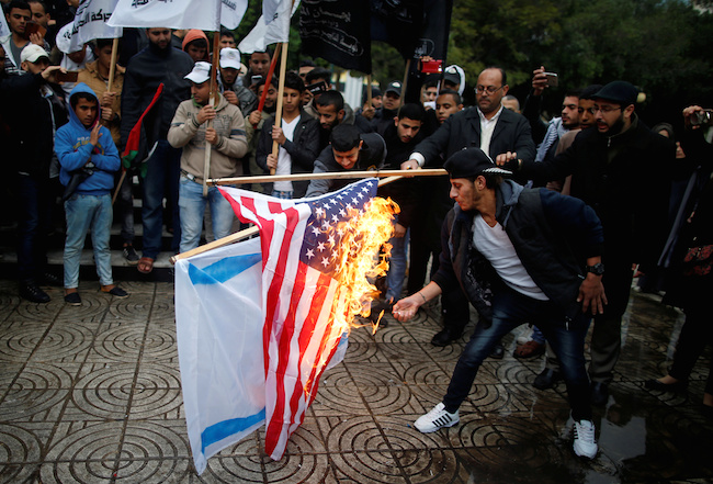 Palestinians burn an Israeli and a U.S. flag during a protest against the U.S. intention to move its embassy to Jerusalem and to recognize the city of Jerusalem as the capital of Israel, in Gaza City December 6, 2017. REUTERS/Mohammed Salem