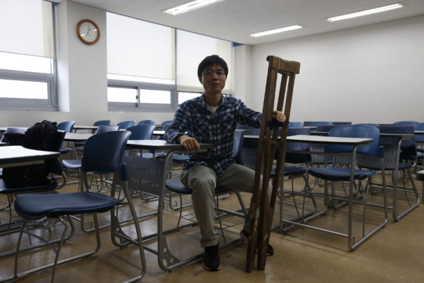 Ji Seong-Ho, 31, who is a North Korean defector living in South Korea and president of Now, Action and Unity for Human Rights (NAUH), poses for a photograph with his handmade wooden crutches, which were used to cross the Tumen River on the border with China, during an interview with Reuters in Seoul, May 29, 2013. From the streets of Seoul to the European parliament a new generation of North Korean defectors is stepping into the limelight, telling their personal stories to highlight the human rights abuses in their homeland. Picture taken May 29, 2013. REUTERS/Kim Hong-Ji