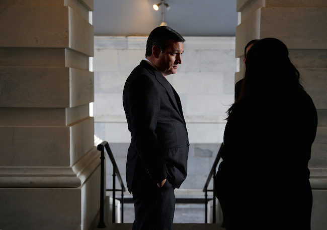 Senator Ted Cruz speaks with an aide before boarding a bus departing to the White House for a bill passage event after the Republicans passed a tax bill, on Capitol Hill in Washington, December 20, 2017. REUTERS/Joshua Roberts