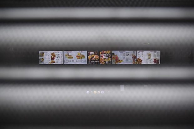 A sign seen through the shutters on a closed KFC fast food store in south London is closed on February 19, 2018 shows the menu. US fast food chain KFC said on February 19 it had been forced to close many restaurants in Britain because of a new supplier failing to deliver chicken in time, generating some tongue-in-cheek outrage on Twitter. / AFP PHOTO / BEN STANSALL (Photo credit should read BEN STANSALL/AFP/Getty Images)