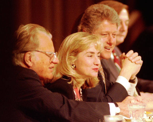 Rev. Billy Graham sits with first lady Hillary Clinton and President Bill Clinton at the head table during a prayer breakfast at the Washington Hilton hotel Feb 04, 1993. REUTERS/Gary Cameron