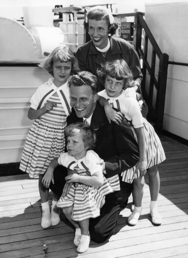 """Billy Graham, 35, the American evangelist, is greeted by his wife and children, Virginia, 8 (L), Anne, 6 (R) and Ruth (Bunny), 3 (foreground) aboard the liner """"Queen Mary"""" on his return to New York June 7, 1954, from a religious tour of Europe. (Photo: AFP/AFP/Getty Images)"""
