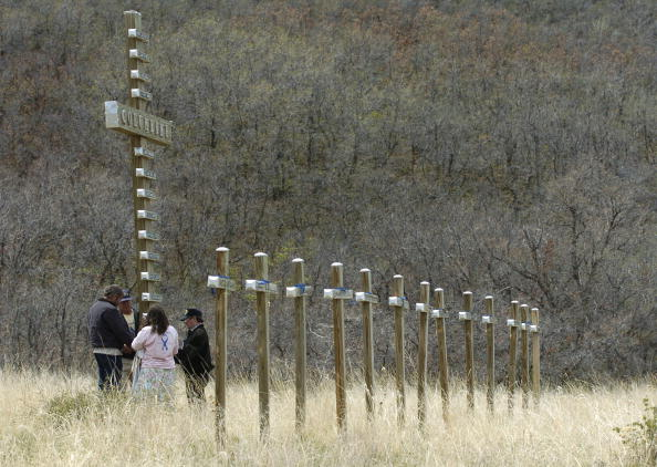 LITTLETON, CO - APRIL 20: Jim Brinks (R-L), Steve Schweltzberger, Ron Aigner, and a woman known only as Golden Eagle stand and pray around the large cross among thirteen small crosses April 20, 2004, that serve as a memorial to the twelve students and one teacher killed in the Columbine High School shootings in Littleton, Colorado on April 20, 1999. This is the five year anniversary of the shooting at Columbine, and these are the original thirteen crosses that were put in Clements Park next to Columbine after after the shooting in 1999. (Photo by Larry W. Smith/Getty Images)