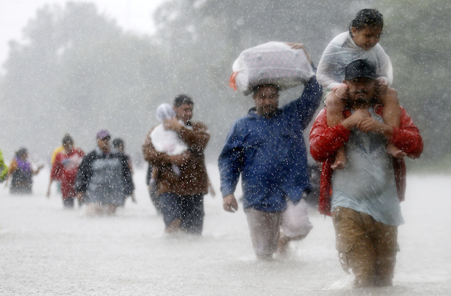 Residents wade through flood waters from Tropical Storm Harvey in Beaumont Place, Houston, August 28, 2017. REUTERS/Jonathan Bachman/File photo