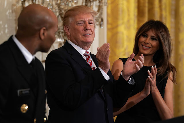 WASHINGTON, DC - FEBRUARY 13: U.S. President Donald Trump (2nd L) and first lady Melania Trump (R) applaud as Surgeon General Jerome Adams (L) looks on during a reception in the East Room of the White House February 13, 2018 in Washington, DC. President Trump and the first lady hosted a reception to celebrate the National African American History Month with leaders and representatives from the African American community. (Photo by Alex Wong/Getty Images)