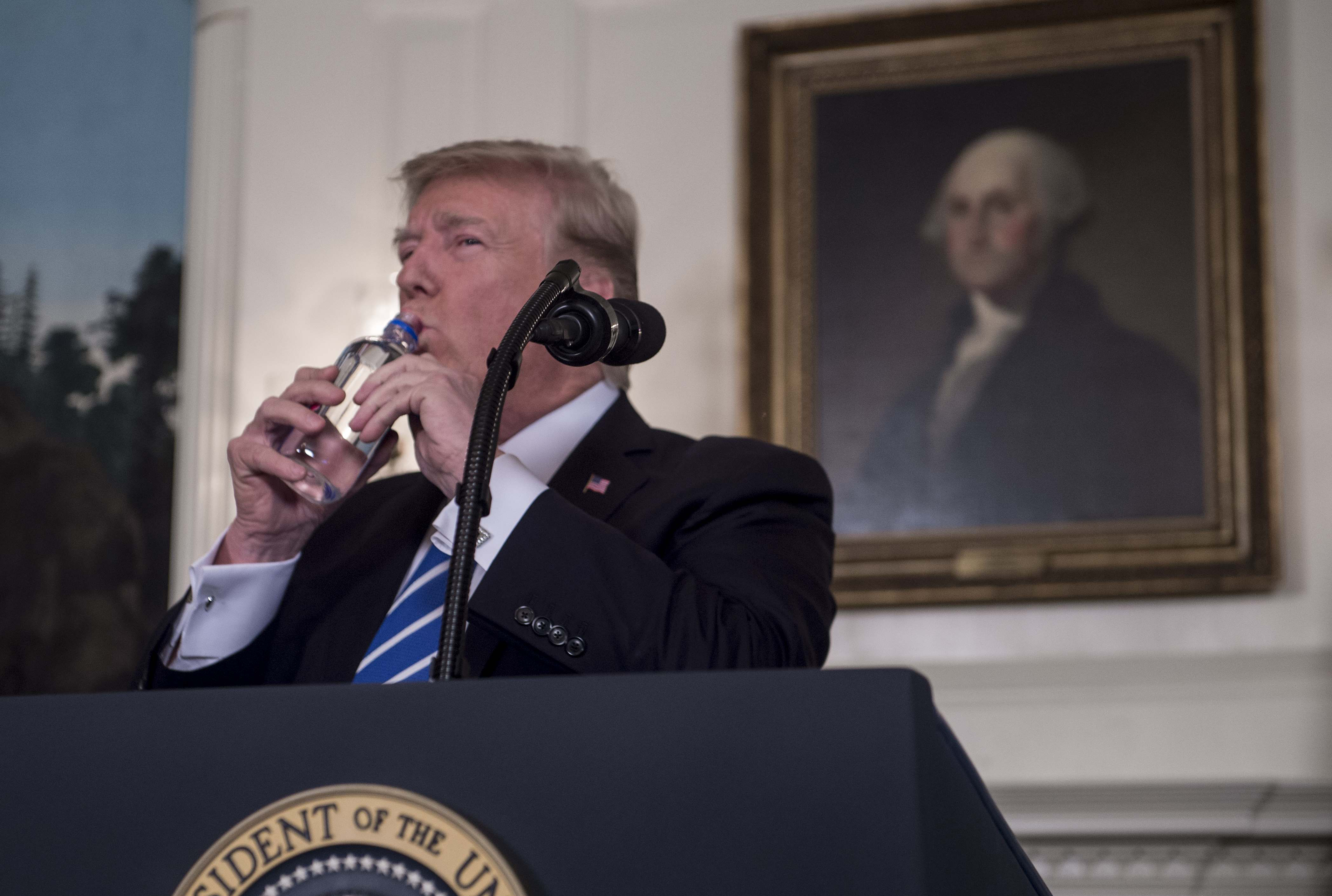 US President Donald Trump drinks water from a bottle as he delivers remarks on November 15, 2017 in the Diplomatic Room at the White House in Washington, DC. At right is a portrait of first US president George Washington. (NICHOLAS KAMM/AFP/Getty Images)