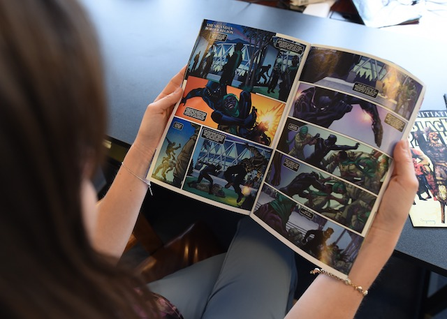 """In this photo illustration a woman reads a copy of the Black Panther (T'Challa) a fictional superhero appearing in comic book published by Marvel Comics in New York May 17, 2016. Captain America and Iron Man may be the stars of Marvel's latest comic-book blockbuster, but Black Panther -- making his big-screen debut -- is most definitely the superhero of the moment. Black Panther, the warrior king of the futuristic fictional African country Wakanda, is starring in a new comic book series that is doing booming sales, and will be the first black hero to get a standalone film, in 2018. The new comic series -- written by acclaimed author Ta-Nehisi Coates, a leading voice on race issues in America -- debuted in April, and so far 330,000 copies of the first issue alone have been sold, according to Marvel. / AFP / TIMOTHY A. CLARY / TO GO WITH AFP STORY BY THOMAS URBAIN-""""Black Panther, Marvel's African hero, in the spotlight"""" (Photo credit should read TIMOTHY A. CLARY/AFP/Getty Images)"""