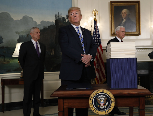 President Donald Trump speaks with Vice President Mike Pence and Defense Secretary Jim Mattis at his side during an event to sign Congress' $1.3 trillion spending bill in the Diplomatic Room of the White House in Washington, March 23, 2018. REUTERS/Kevin Lamarque