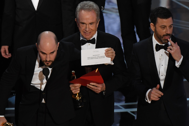 "US actor Warren Beatty (C) shows the card reading Best Film 'Moonlight"" next to ""La La Land"" producer Jordan Horowitz (L) and host Jimmy Kimmel after mistakingly reading ""La La Land"" initially at the 89th Oscars on February 26, 2017 in Hollywood, California. / AFP / Mark RALSTON (Photo credit should read MARK RALSTON/AFP/Getty Images)"
