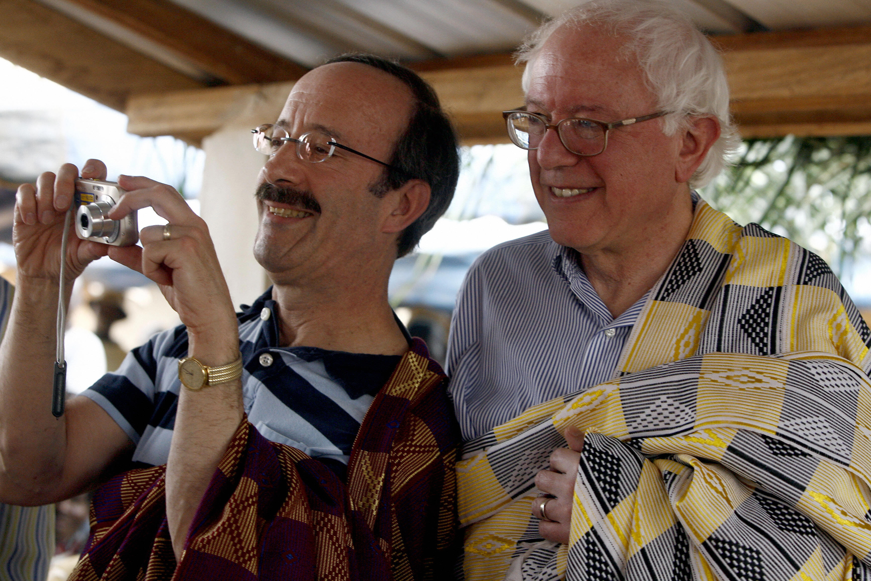 US Congressman Elliot Engel (L) takes pictures next to US Senator Bernie Sanders after being dressed as Bouale leaders by public notaries of the Kouadioyaokro village, 150 km from Abidjan, 09 November 2008. US Senators Tom Harkin and Bernie Sanders visit comes ahead of a July 2008 certification deadline to ensure cocoa heading to the United States -- the third largest importer of Ivorian cocoa -- has not been produced with child labour. (ISSOUF SANOGO/AFP/Getty Images)