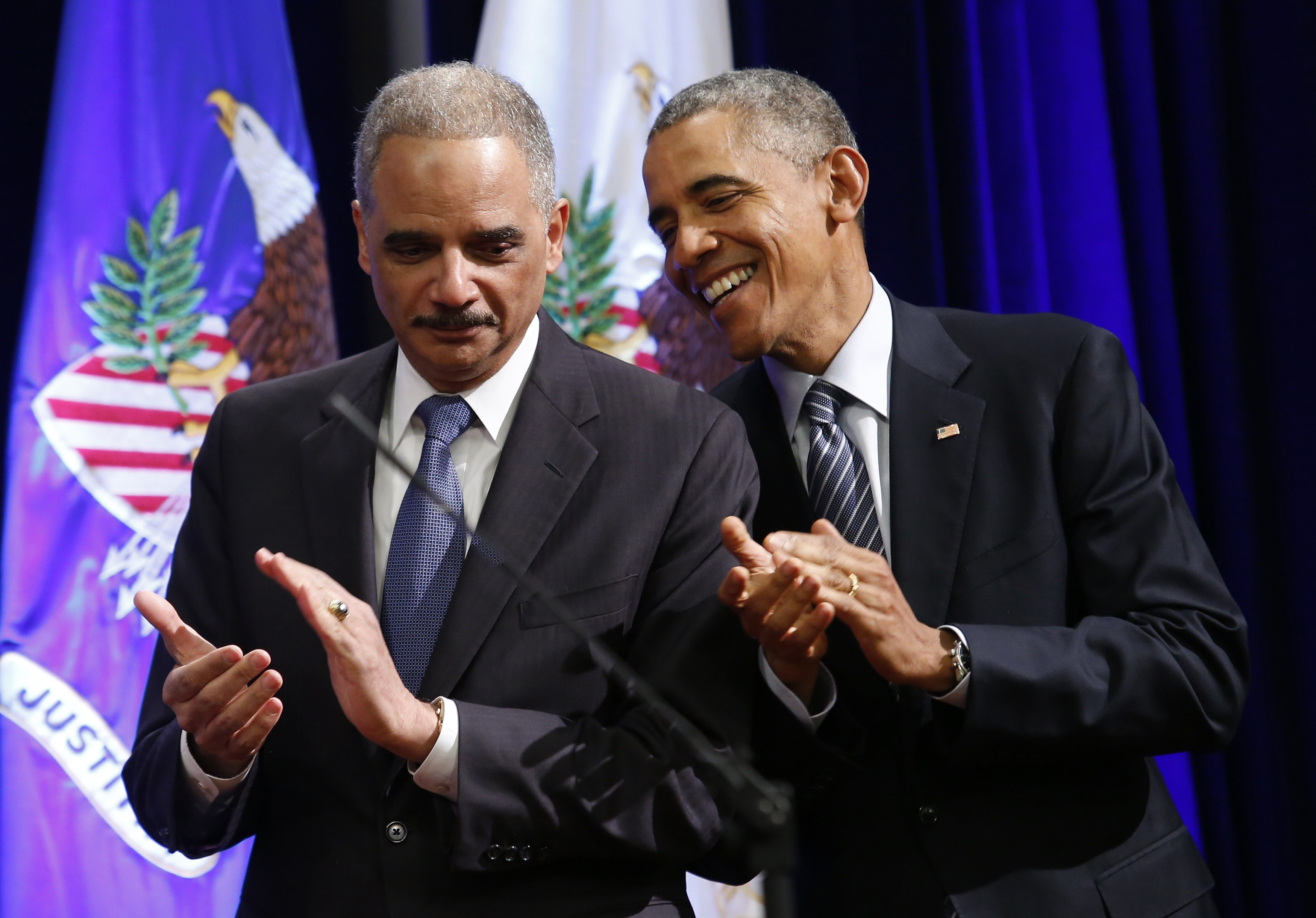 US President Barack Obama (R) talks to outgoing Attorney General Eric Holder at the portrait unveiling ceremony at the Justice Department in Washington, DC on February 27, 2015. The event marks Holder's anticipated departure after more than six years of service. (YURI GRIPAS/AFP/Getty Images)