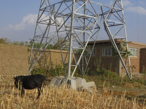 A power line transmission tower built over an occupied farmhouse. The power line could be hazardous to residents if it were turned on (Photo: SIGAR)