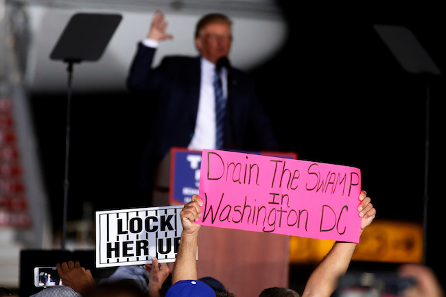 "A man holds up a ""Drain the Swamp in Washington DC"" sign as Republican presidential nominee Donald Trump attends a campaign event on the tarmac of the airport in Kinston, North Carolina, October 26 2016. REUTERS/Carlo Allegri"