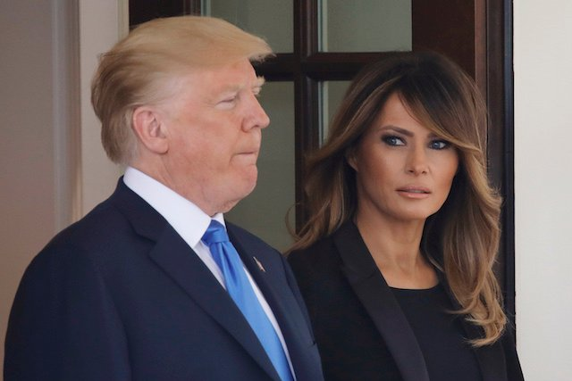 First lady Melania Trump looks over at U.S. President Donald Trump as they wait at the West Wing door to welcome French President Emmanuel Macron and his wife Brigitte Macron at the White House in Washington, U.S., April 23, 2018, REUTERS/Carlos Barria - HP1EE4N1O0LWT