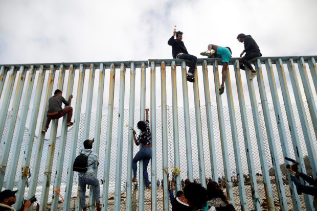 Members of a caravan of migrants from Central America climb up the border fence between Mexico and the U.S., as a part of a demonstration prior to preparations for an asylum request in the U.S., in Tijuana, Mexico April 29, 2018. REUTERS/Edgard Garrido