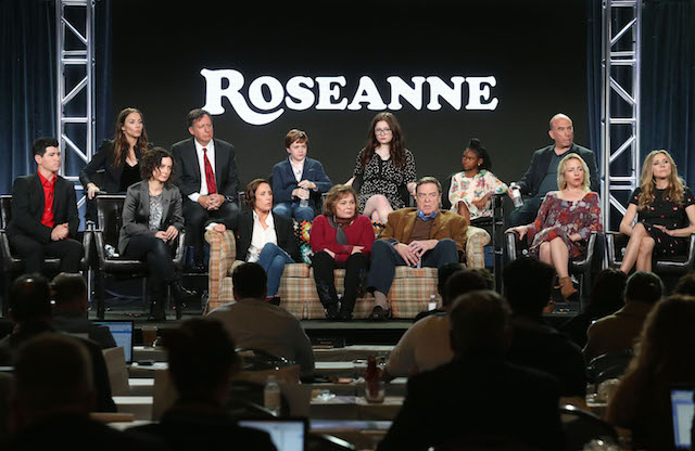 PASADENA, CA - JANUARY 08: (L-R, Back Row) Executive producers Whitney Cummings and Tom Werner, actors Ames McNamera, Emma Kenney, Jayden Rey, executive producer Bruce Helford, (l-r, front row) actor Michael Fishman, executive producer/actress Sara Gilbert, actress Laurie Metcalf, executive producer/actress Roseanne Barr, actors John Goodman, Lecy Goranson and Sarah Chalke of the television show Roseanne speak onstage during the ABC Television/Disney portion of the 2018 Winter Television Critics Association Press Tour at The Langham Huntington, Pasadena on January 8, 2018 in Pasadena, California. (Photo by Frederick M. Brown/Getty Images)