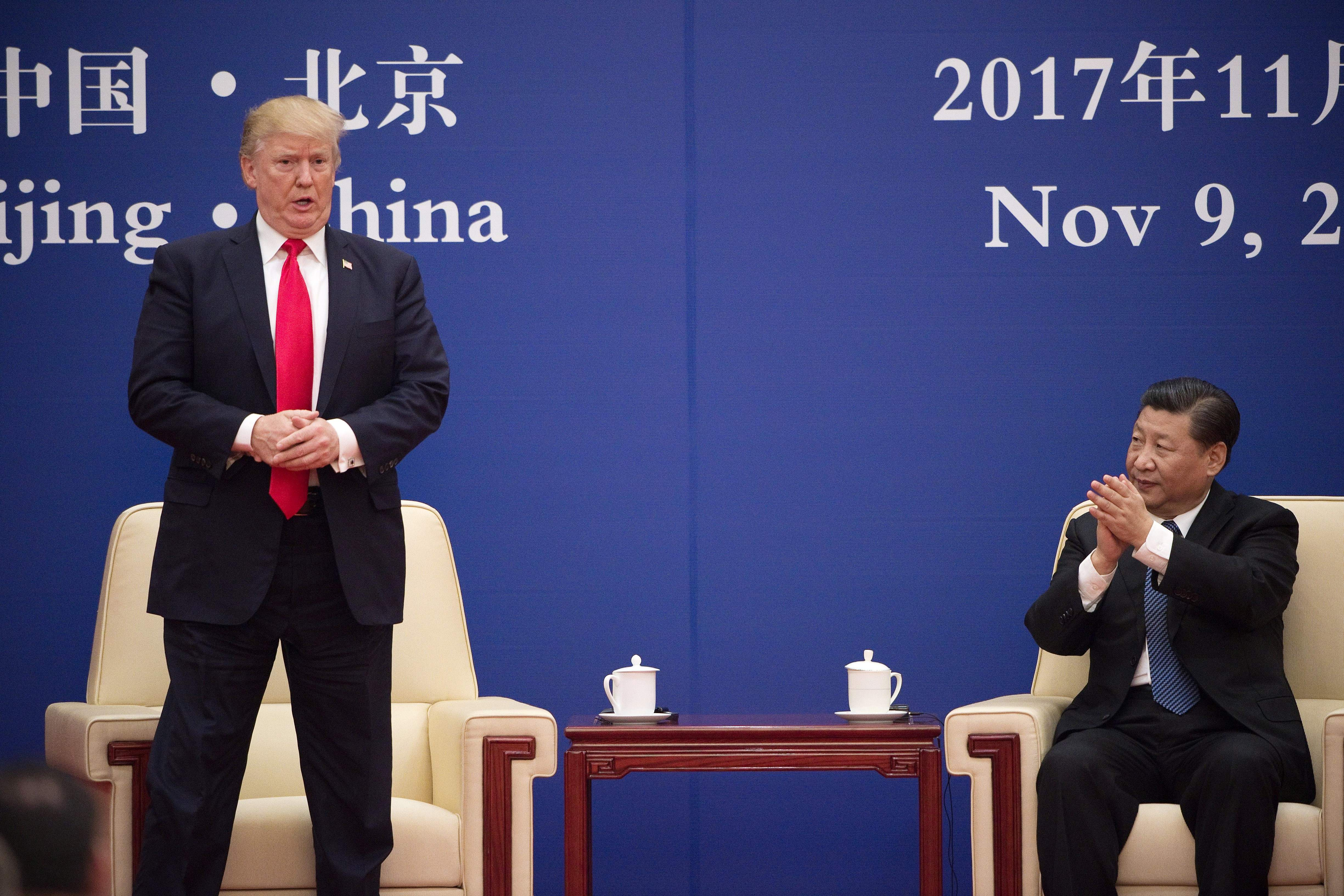 "US President Donald Trump stands during a business leaders event and is applauded by China's President Xi Jinping inside the Great Hall of the People in Beijing on November 9, 2017. Donald Trump urged Chinese leader Xi Jinping to work ""hard"" and act fast to help resolve the North Korean nuclear crisis during their meeting in Beijing, warning that ""time is quickly running out."" (Photo: NICOLAS ASFOURI/AFP/Getty Images)"