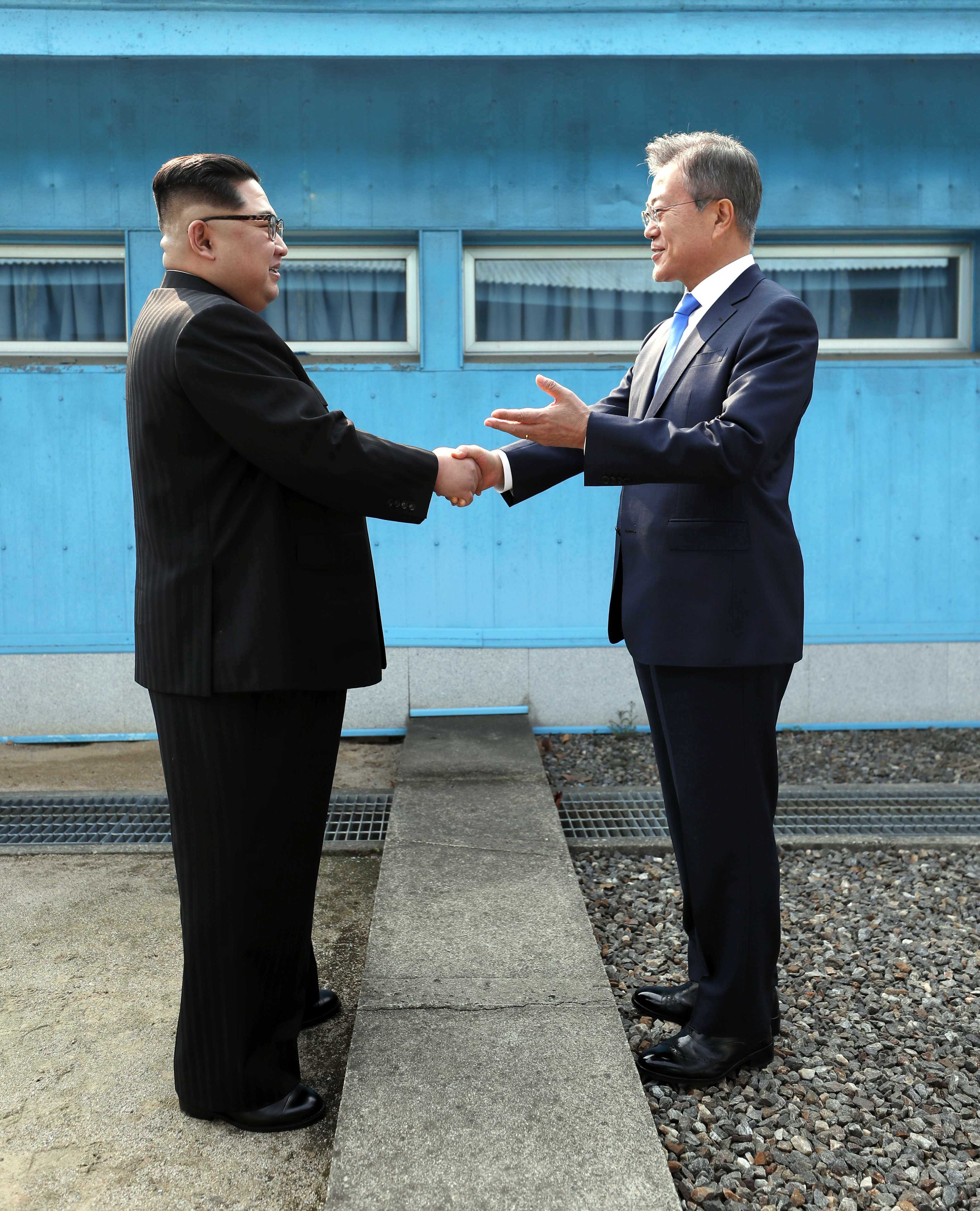 PANMUNJOM, SOUTH KOREA - APRIL 27: North Korean Leader Kim Jong Un (L) and South Korean President Moon Jae-in (R) shake hands over the military demarcation line upon meeting for the Inter-Korean Summit on April 27, 2018 in Panmunjom, South Korea. Kim and Moon meet at the border today for the third-ever inter-Korean summit talks after the 1945 division of the peninsula, and first since 2007 between then President Roh Moo-hyun of South Korea and Leader Kim Jong-il of North Korea. (Photo by Pool/Getty Images)