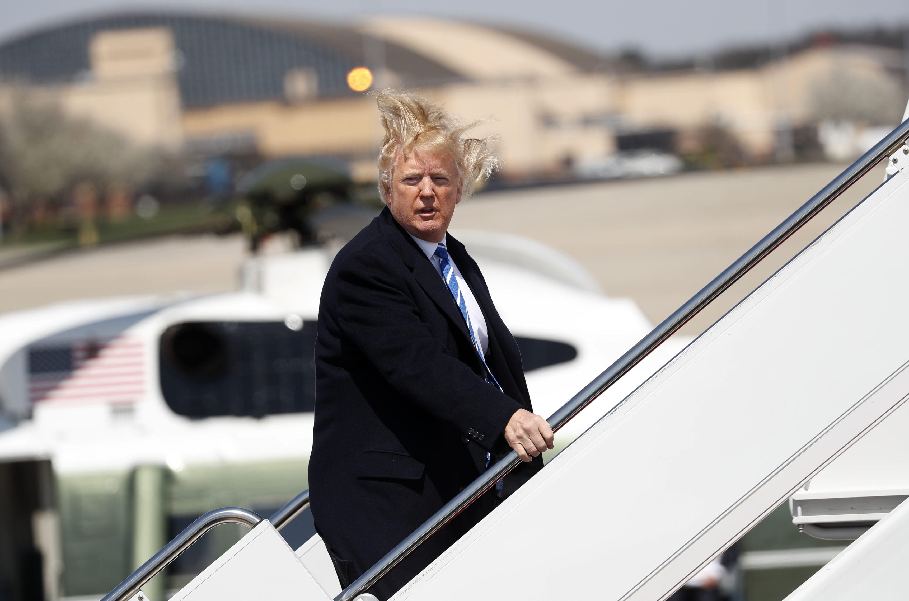 U.S. President Donald Trump yells over to members of the news media as he boards Air Force One on a windy day at Joint Base Andrews, Maryland before departing en route to an event in West Virginia, U.S., April 5, 2018. (REUTERS/Kevin Lamarque)