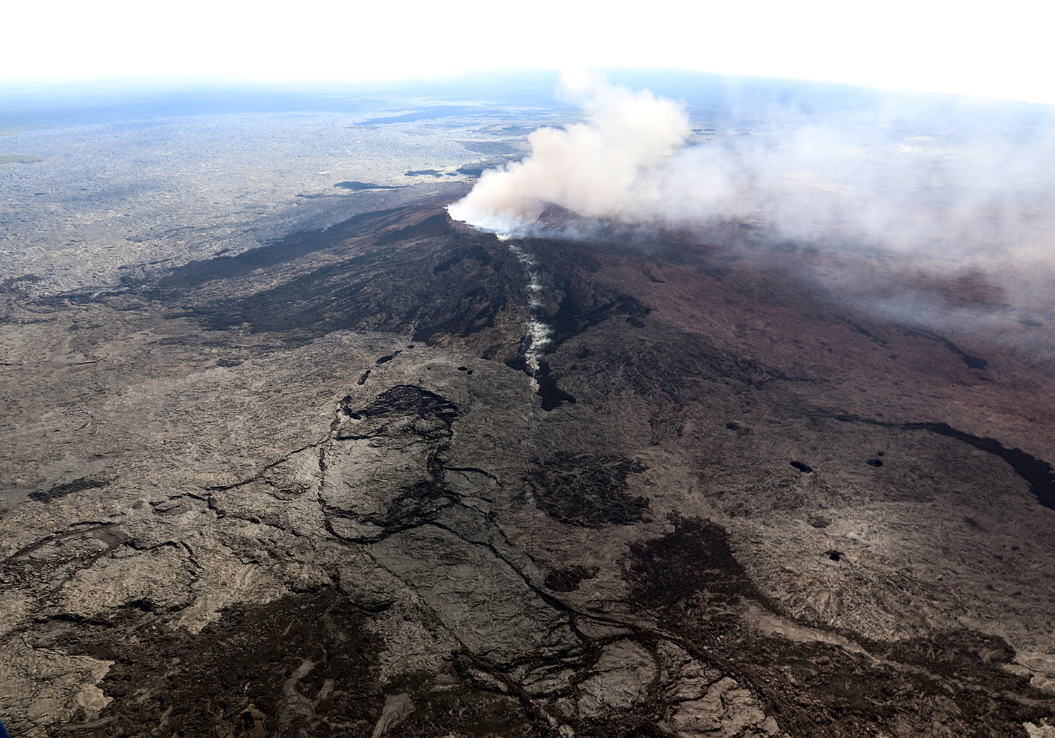The Kilauea Volcano fissure that formed on the west flank of the Pu'u 'O'o cone (line of white steam) is seen in this aerial image after the volcano erupted following a series of earthquakes over the last couple of days, in Hawaii, U.S. on May 3, 2018. Picture taken on May 3, 2018. USGS/Handout via REUTERS