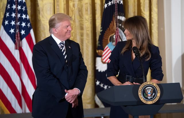 US President Donald Trump stands alongside First Lady Melania Trump (R) during an event in honor of Military Mothers and Spouses in the East Room of the White House in Washington, DC, May 9, 2018. (Photo by SAUL LOEB / AFP) (Photo credit should read SAUL LOEB/AFP/Getty Images)