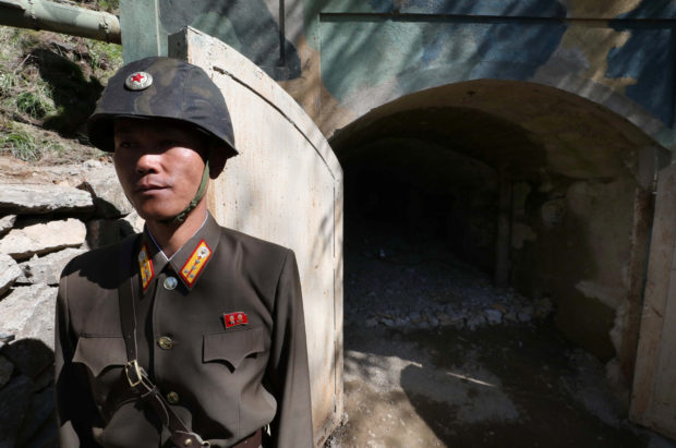 A North Korean soldier stands guard in front of the second tunnel of Punggye-ri nuclear test ground before it is blown up during the dismantlement process in Punggye-ri, North Hamgyong Province, North Korea May 24, 2018. News1/Pool via REUTERS