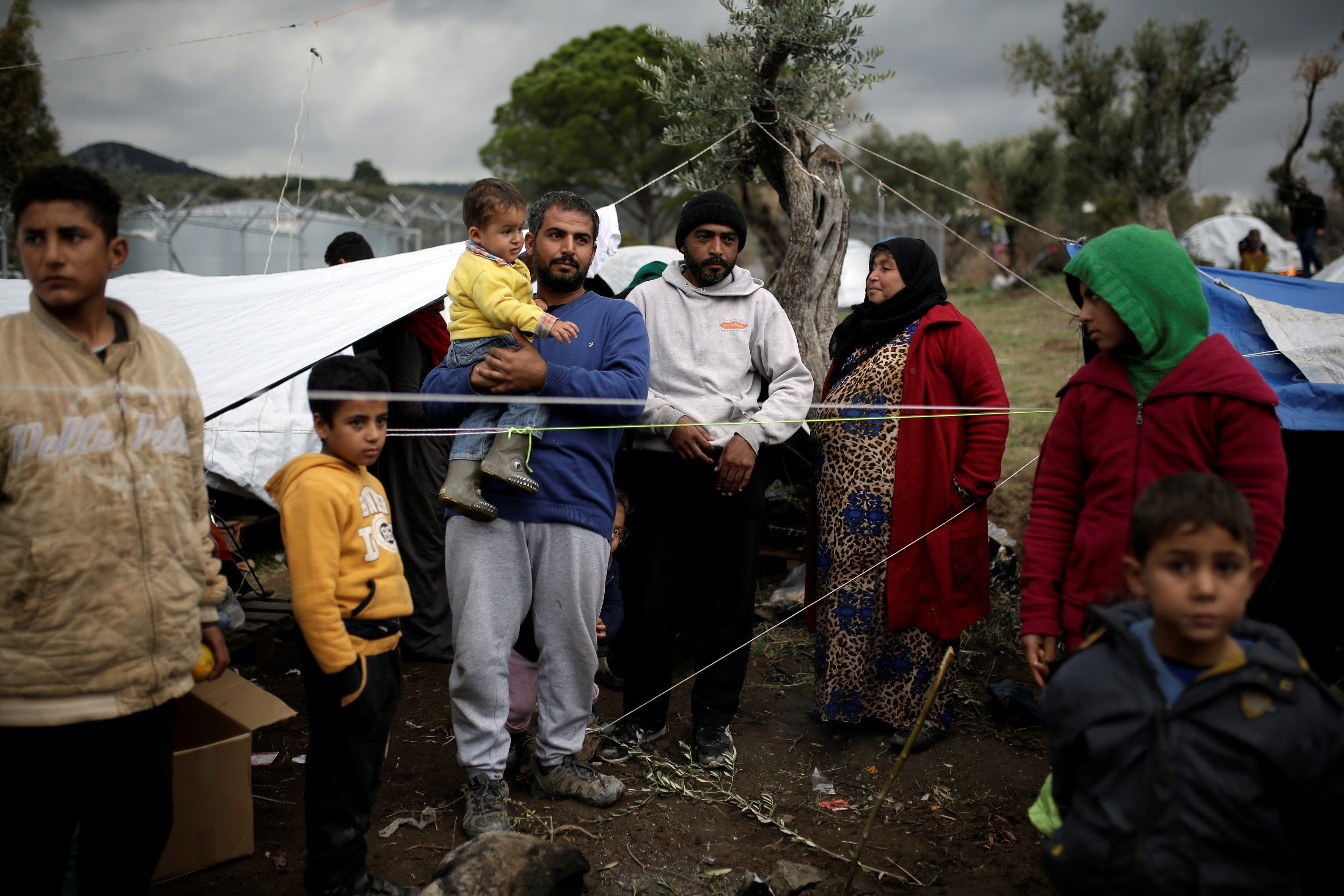 "Syrian refugee Bashar Wakaa (3rd L) and his family stand in front of their tents at a makeshift camp for refugees and migrants next to the Moria camp on the island of Lesbos, Greece, November 30, 2017. REUTERS/Alkis Konstantinidis SEARCH ""MORIA CAMP"" FOR THIS STORY. SEARCH ""WIDER IMAGE"" FOR ALL STORIES. - RC1F728A1580"