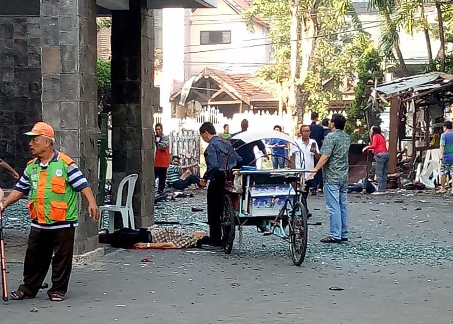 Bystanders observe the aftermath of a suicide bombing at a church in Surabaya, Indonesia on May 13, 2018. PHOTO: TheDCNF