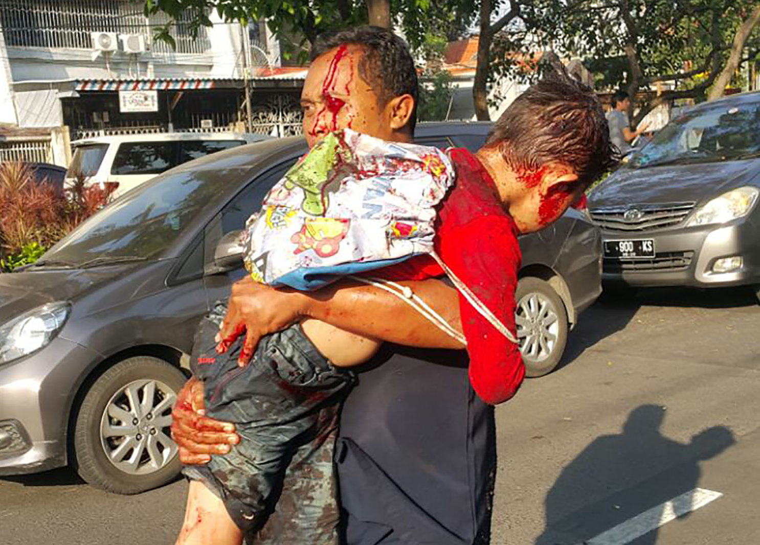 A man carries an injured child away from the scene of a suicide bombing at a church in Surabaya, Indonesia on May 13, 2018. PHOTO: TheDCNF