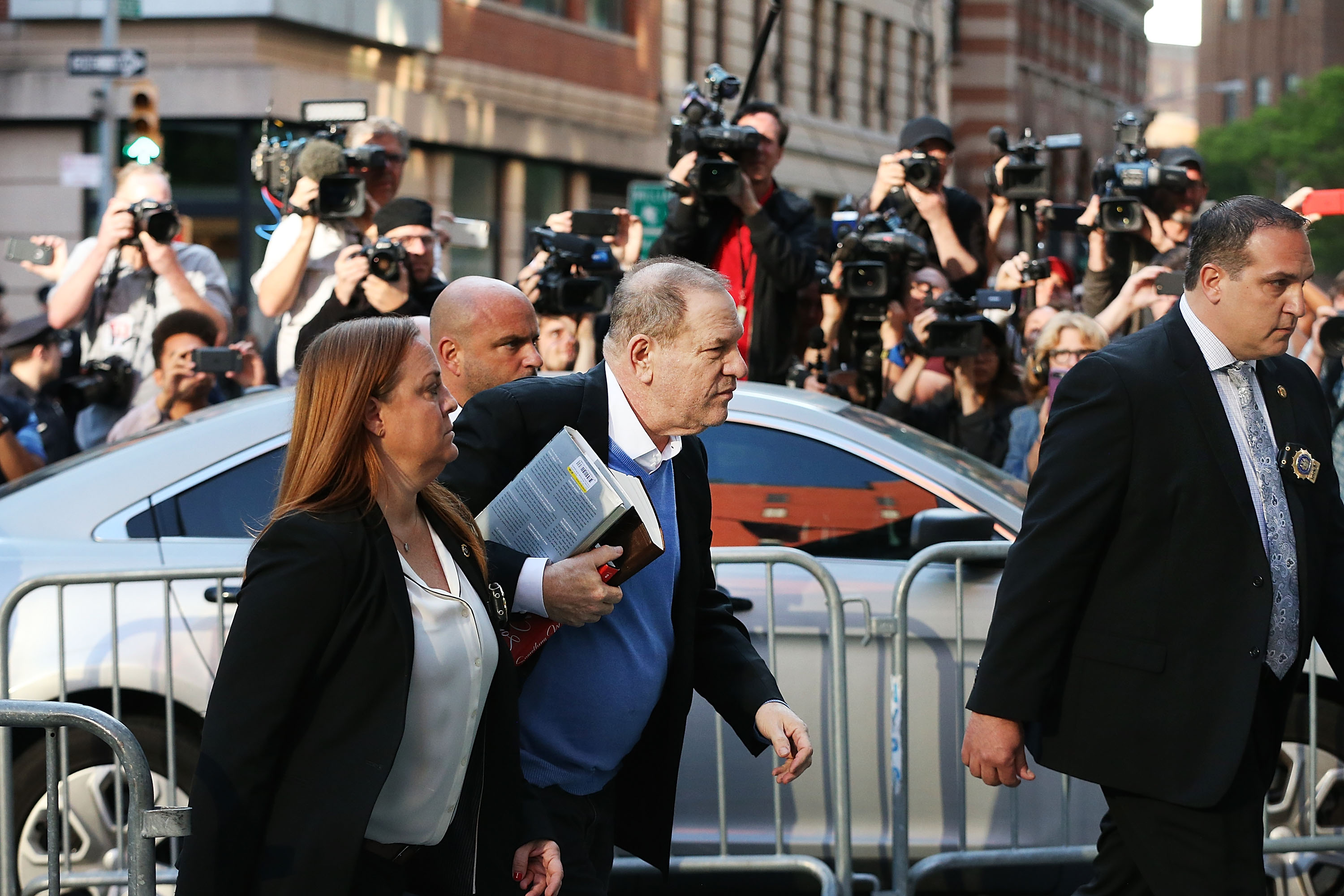 NEW YORK, NY - MAY 25: Harvey Weinstein arrives at the New York Police Department's First Precinct to turn himself in after being served with criminal charges by the Manhattan District Attorney's office on May 25, 2018 in New York City. The former movie producer faces charges in connection with accusations made by aspiring actress Lucia Evans who has said that Weinstein forced her to perform oral sex on him in his Manhattan office in 2004. Weinstein (66) has been accused by dozens of other women of forcing them into sexual acts using both pressure and threats. The revelations of his behavior helped to spawn the global #MeToo movement. Weinstein is carrying a biography of Elia Kazan. (Photo by Spencer Platt/Getty Images)