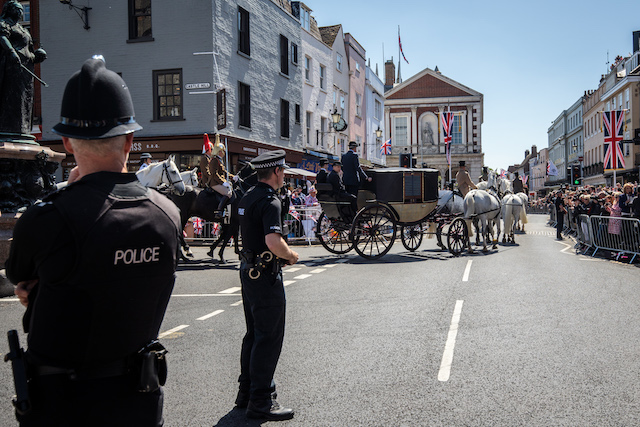 WINDSOR, ENGLAND - MAY 17: Police officers look on as a carriage is pulled by four Windsor Grey horses from Windsor Castle during a dress rehearsal of the wedding of Prince Harry and Meghan Markle outside Windsor Castle on May 17, 2018 in Windsor, England. (Photo by Jack Taylor/Getty Images)