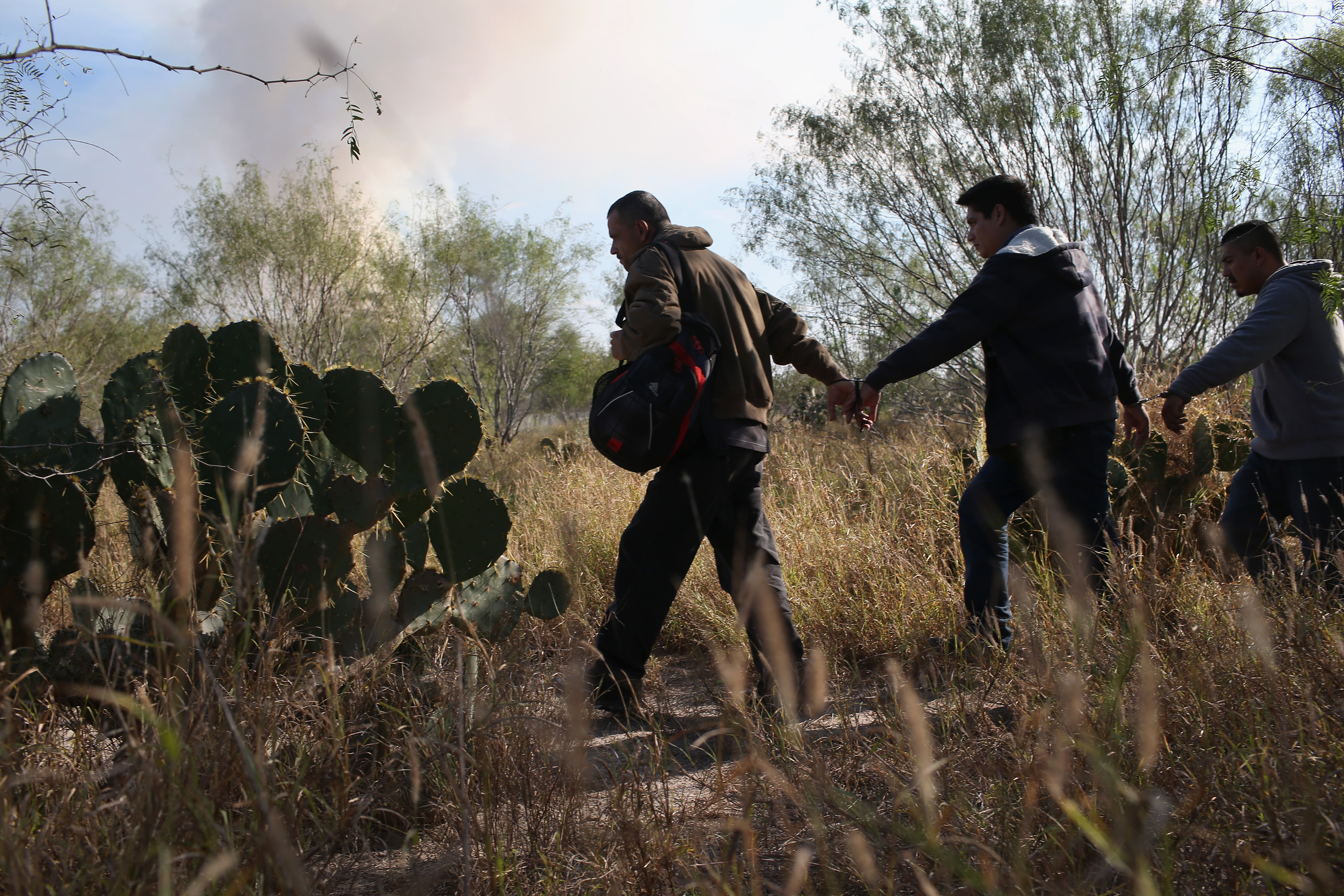 RIO GRANDE CITY, TX - DECEMBER 07: Immigrants walk handcuffed after illegally crossing the U.S.-Mexico border and being caught by the U.S. Border Patrol on December 7, 2015 near Rio Grande City, Texas. Border Patrol agents continue to capture hundreds of thousands of undocumented immigrants, even as the total numbers of those crossing has gone down. (Photo by John Moore/Getty Images)