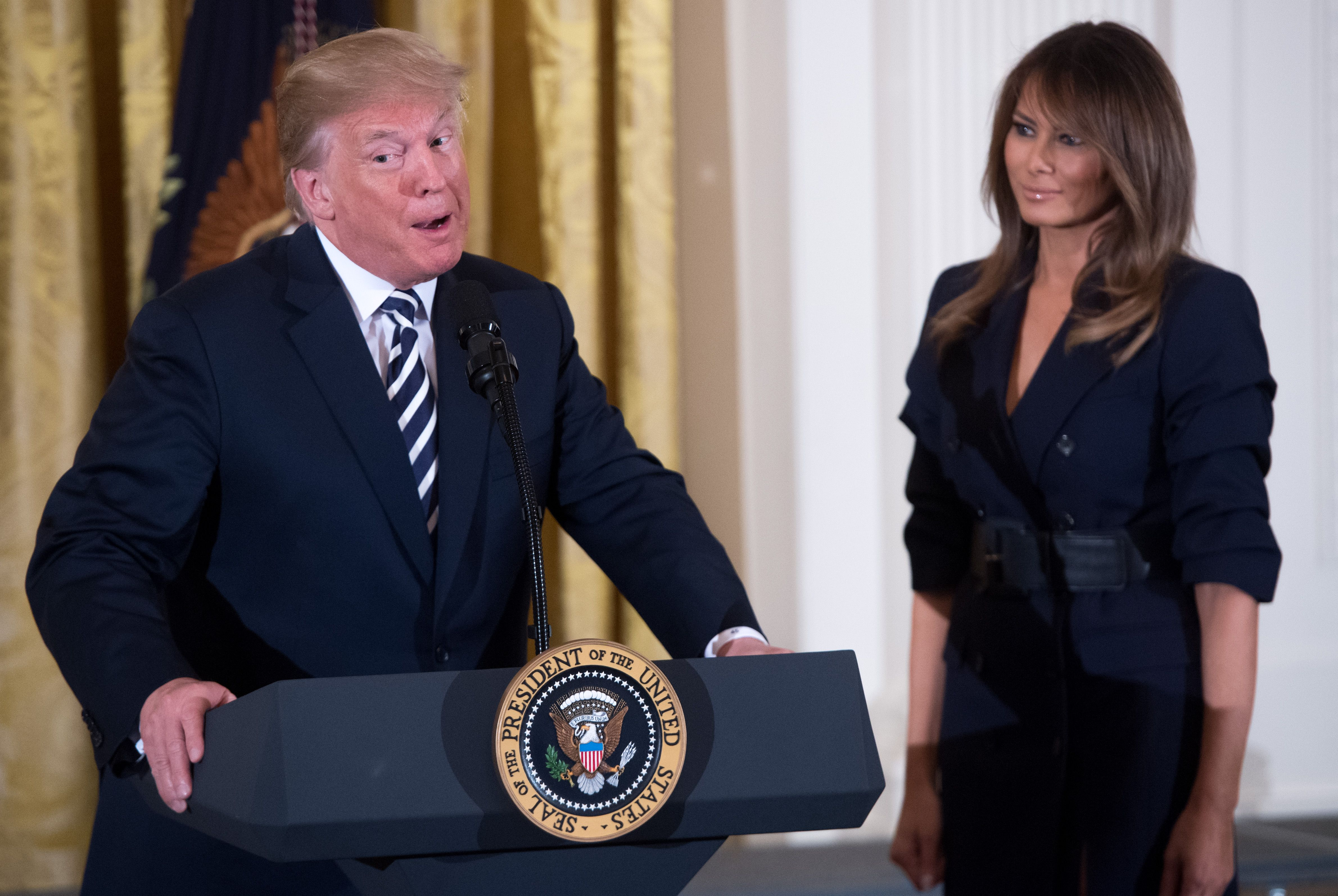 US President Donald Trump speaks alongside First Lady Melania Trump (R) during an event in honor of Military Mothers and Spouses in the East Room of the White House in Washington, DC, May 9, 2018. (Photo by SAUL LOEB / AFP) (Photo credit should read SAUL LOEB/AFP/Getty Images)
