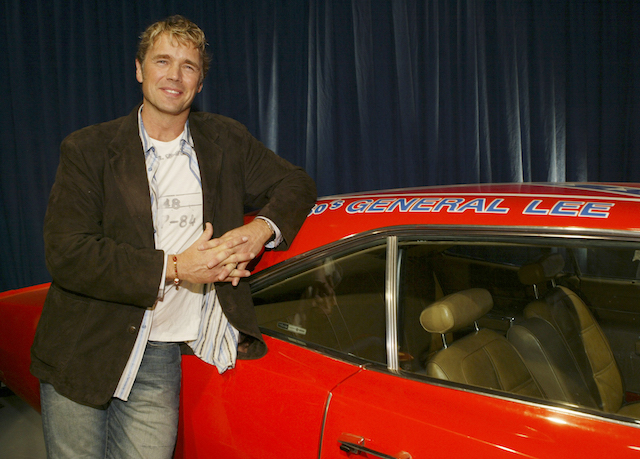 """Actor John Schneider poses with the """"General Lee"""" car from """"The Dukes of Hazard"""" televison show he starred in during the """"Warner Brothers Television and Warner Home Video Celebrate 50 Years of Quality TV"""" party at Warner Brothers Studio in Burbank, California, January 20, 2005. REUTERS/Lee Celano SSM - RP5DRIESGAAA"""