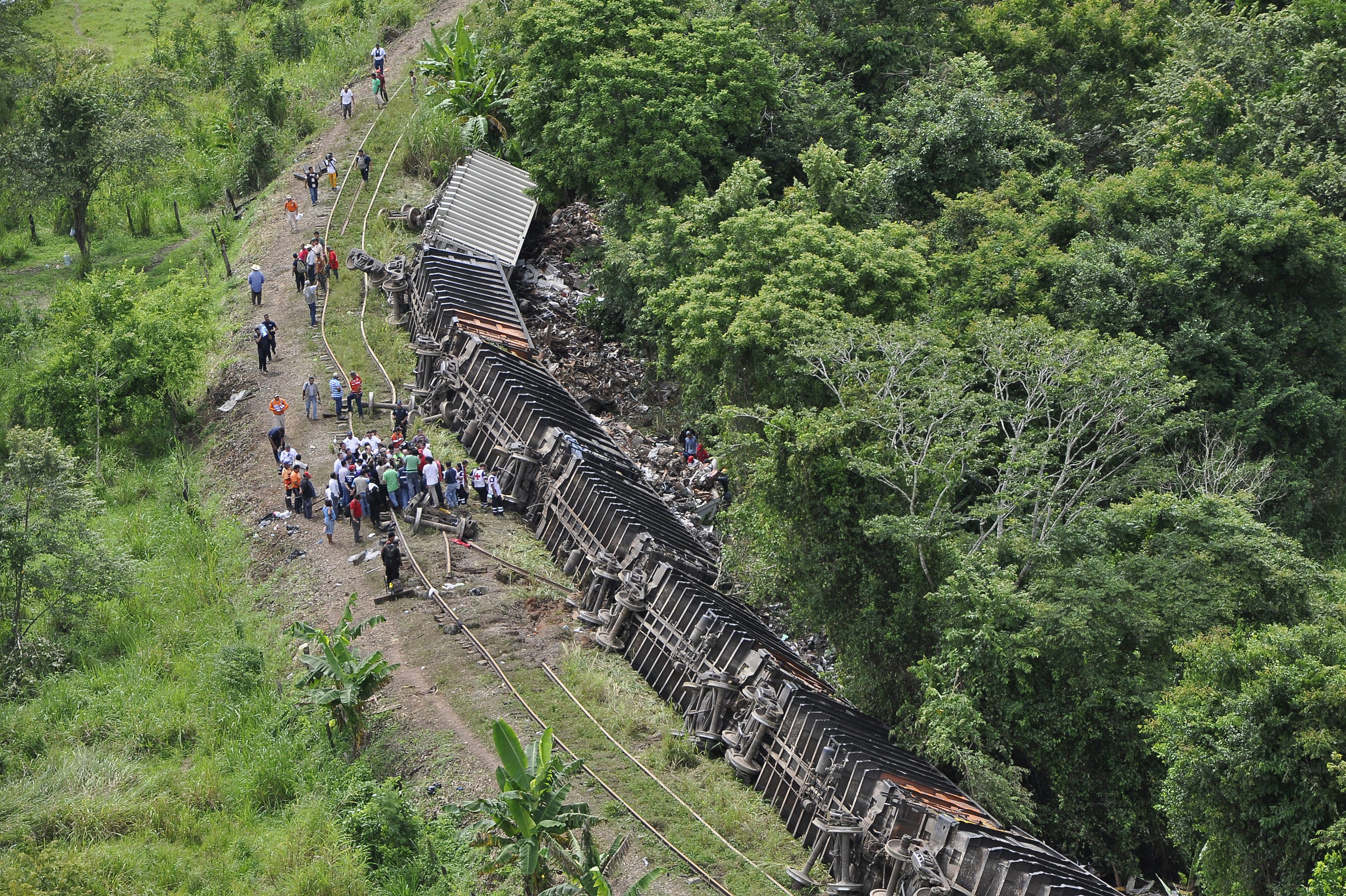 "Railroad workers and police investigators stand near the overturned carriages of a derailed train in Huimanguillo, in the Mexican state of Tabasco August 25, 2013. At least six people were killed when a cargo train nicknamed ""La Bestia,"" or ""The Beast,"" on which would-be migrants hitch rides toward the U.S. border, derailed in a remote area of southern Mexico on Sunday, state officials said. REUTERS/Luis Manuel Lopez"