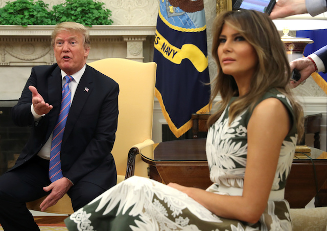 U.S. President Donald Trump speaks next to first lady Melania Trump in the Oval Office as the meet with Spain's King Felipe VI (L) and Queen Letizia (R) at the White House in Washington, U.S., June 19, 2018. REUTERS/Jonathan Ernst