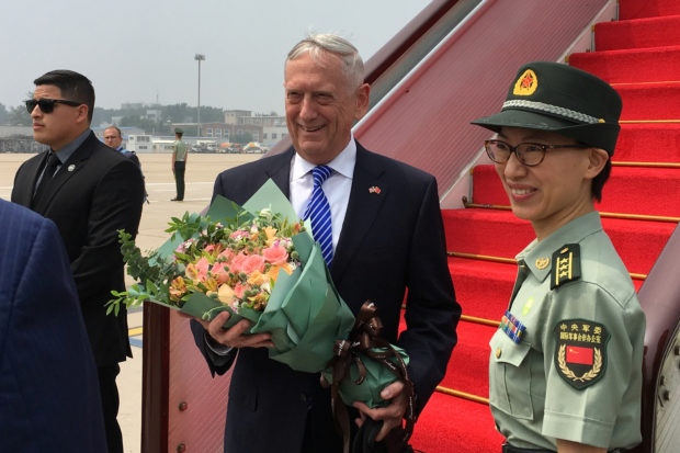 U.S. Defense Secretary Jim Mattis receives a bouquet upon arrival at an airport in Beijing, China June 26, 2018. REUTERS/Phil Stewart