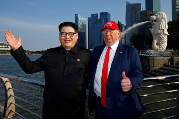 Howard, an Australian-Chinese impersonating North Korean leader Kim Jong-un, and Dennis Alan, impersonating U.S. President Donald Trump, meet at Merlion Park in Singapore June 8, 2018. REUTERS/Edgar Su