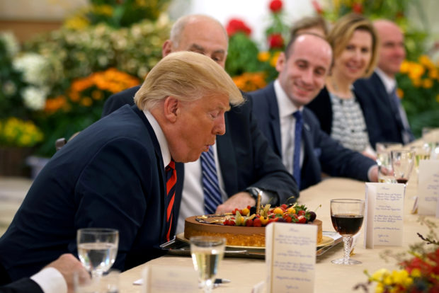 U.S. President Donald Trump blows out the candle on his birthday cake as he attends a lunch with Singapore's Prime Minister Lee Hsien Loong at the Istana in Singapore June 11, 2018. Mandatory credit Ministry of Communications and Information, Singapore/Handout via REUTERS