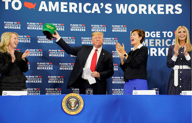 """President Donald Trump holds up a """"Make Our Farmers Great Again"""" cap next to Iowa Governor Kim Reynolds (2ndR) and White House senior advisor Ivanka Trump (R) while taking part in a roundtable discussion on workforce development at Northeast Iowa Community College in Peosta, Iowa, U.S., July 26, 2018. REUTERS/Joshua Roberts"""