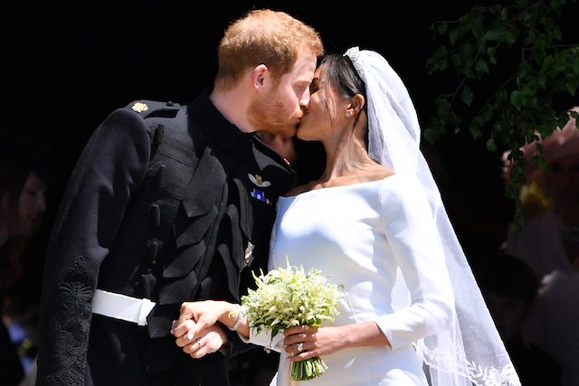 Britain's Prince Harry, Duke of Sussex kisses his wife Meghan, Duchess of Sussex as they leave from the West Door of St George's Chapel, Windsor Castle, in Windsor, on May 19, 2018 after their wedding ceremony. (Photo credit: STANSALL/AFP/Getty Images)