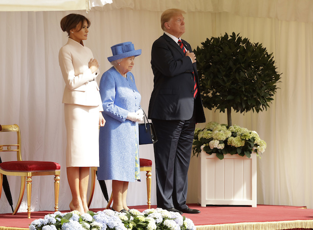 Queen Elizabeth II stands with President of the United States, Donald Trump and First Lady, Melania Trump for their national anthem at Windsor Castle on July 13, 2018 in Windsor, England. Her Majesty welcomed the President and Mrs Trump at the dais in the Quadrangle of the Castle. A Guard of Honour, formed of the Coldstream Guards, gave a Royal Salute and the US National Anthem was played. The Queen and the President inspected the Guard of Honour before watching the military march past. The President and First Lady then joined Her Majesty for tea at the Castle. (Photo by Matt Dunham - WPA Pool/Getty Images)