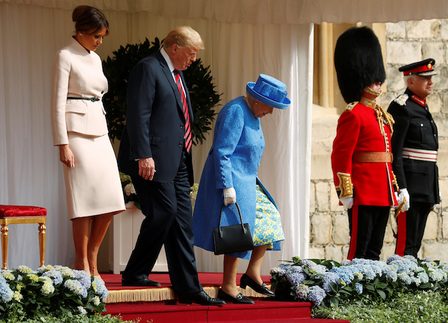 The First Lady Melania Trump waits as U.S. President Donald Trump and Britain's Queen Elizabeth walk across the courtyard to inspect the Coldstream Guards during a visit to Windsor Castle in Windsor, Britain, July 13, 2018. REUTERS/Kevin Lamarque