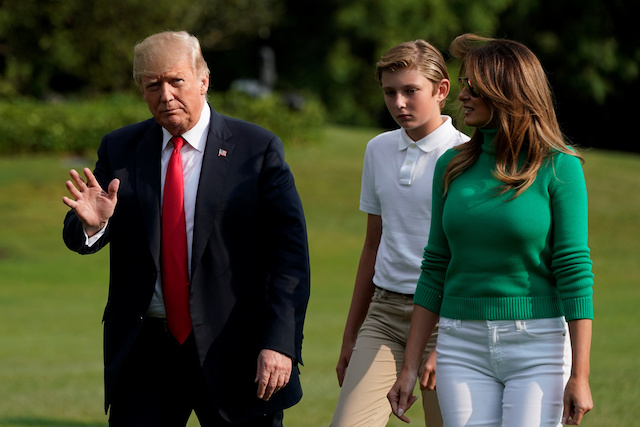 U.S. President Donald Trump waves to the media as he walk with first lady Melania Trump and their son Barron on the South Lawn of the White House upon their return from Bedminster, New Jersey, to Washington, U.S., August 19, 2018. REUTERS/Yuri Gripas