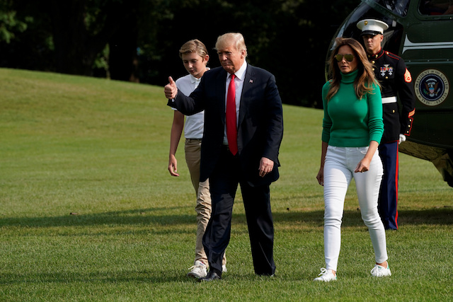 U.S. President Donald Trump gestures as he walk with first lady Melania Trump and their son Barron on the South Lawn of the White House upon their return from Bedminster, New Jersey, to Washington, U.S., August 19, 2018. REUTERS/Yuri Gripas